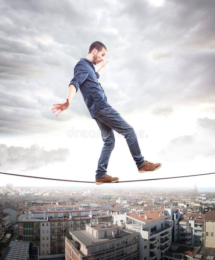 Jonge mens die op een kabel in evenwicht lopen stock fotografie