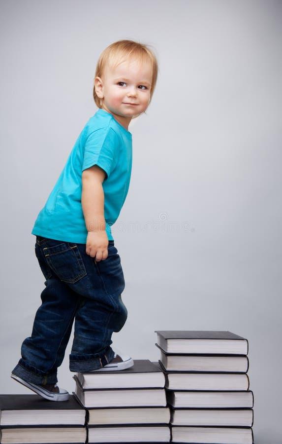 Jonge mens die op een ladder van boeken beklimt stock fotografie