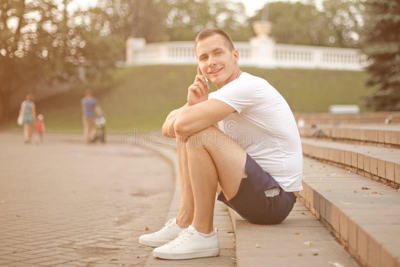 Jonge mens die op een mobiele telefoon spreken, die op de stappen in het stadspark zitten stock afbeeldingen