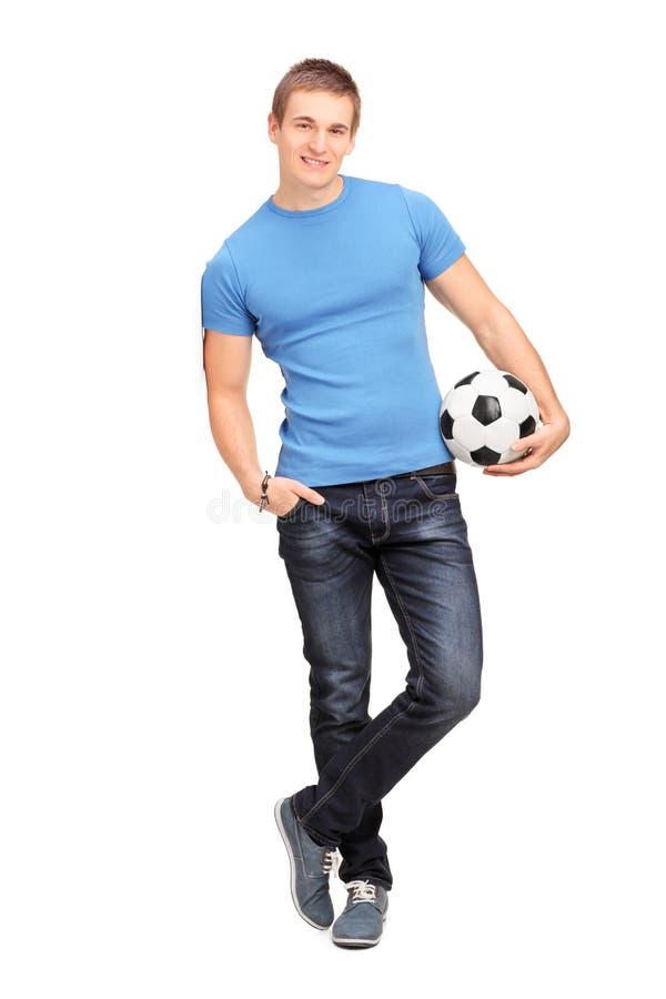 Jonge mens die op een muur leunen en een bal houden stock afbeelding