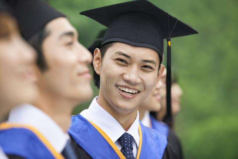 Jonge Mens die op een rij van Jonge Universitaire Gediplomeerden glimlachen royalty-vrije stock fotografie