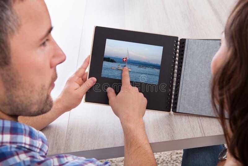 Jonge mens die op fotoalbum richten stock foto