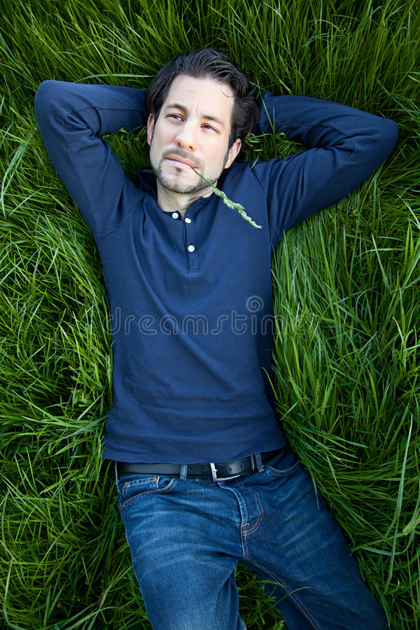 Jonge mens die op groene gras liggen stock foto's