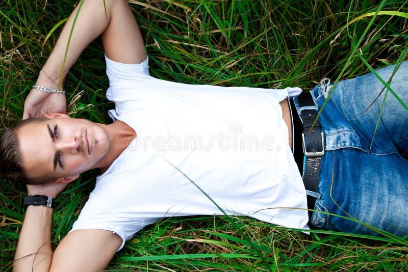 Jonge mens die op groene gras liggen royalty-vrije stock foto's