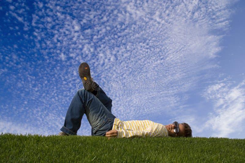 Jonge mens die op het gras ligt stock foto