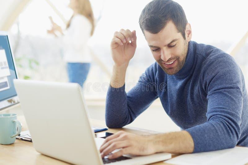 Jonge mens die op het kantoor werken stock afbeelding