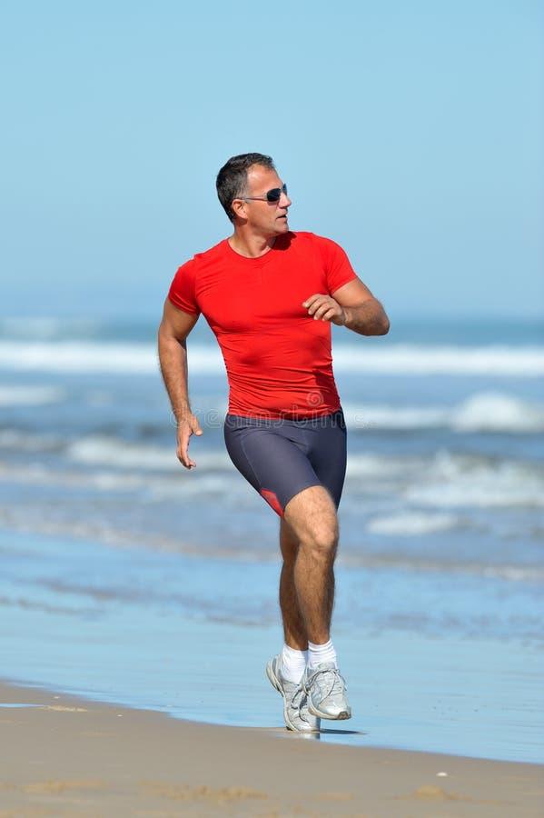 Jonge mens die op het strand aanstoot stock fotografie