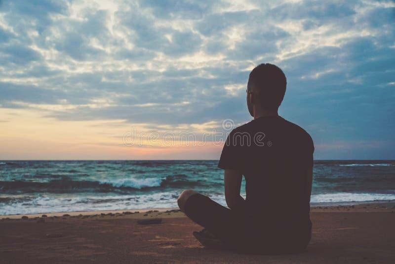 Jonge mens die op hoogste oceaanklip tijdens zonsondergang mediteren stock foto