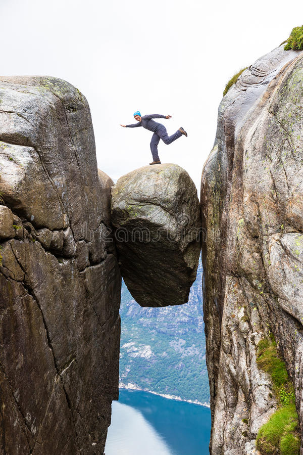 Jonge mens die op kjerag wandelen Gelukkig geniet van mooi meer en goed weer in Noorwegen royalty-vrije stock afbeelding