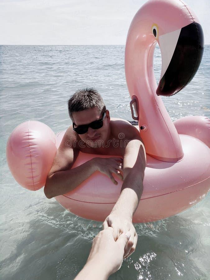 Jonge mens die op opblaasbare roze flamingo in een overzees zwemmen royalty-vrije stock afbeeldingen