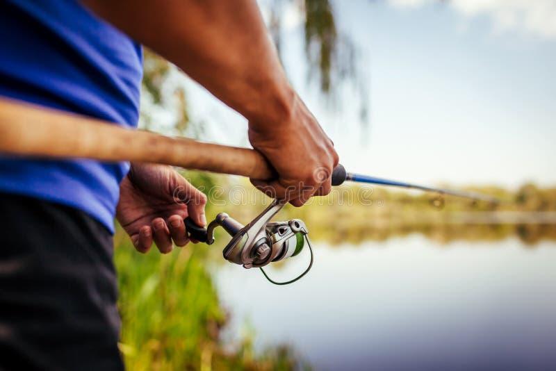 Jonge mens die op rivier bij zonsondergang vissen Close-up van fiserman holdingsstaaf als volkswijsheid spinning stock foto