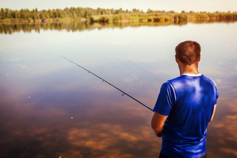 Jonge mens die op rivierbank vissen Visser die van hobby genieten spinning stock foto