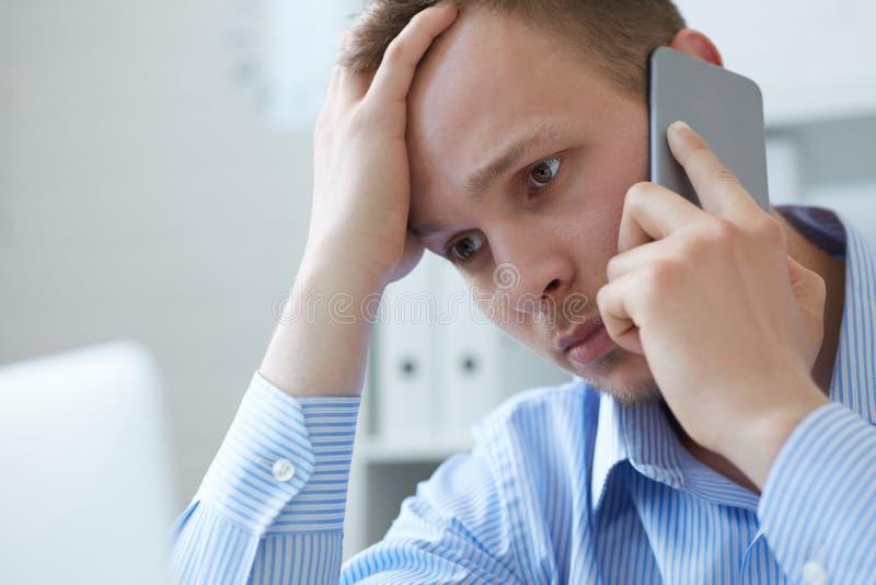 Jonge mens die op smartphone spreken Vermoeide zakenmanmens die mobiele telefoon met behulp van terwijl het bekijken het bureauco royalty-vrije stock afbeeldingen
