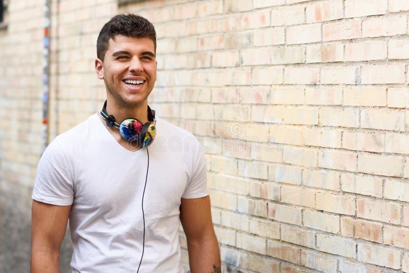 Jonge mens die op stedelijke achtergrond aan muziek met hoofdtelefoons luisteren stock afbeeldingen