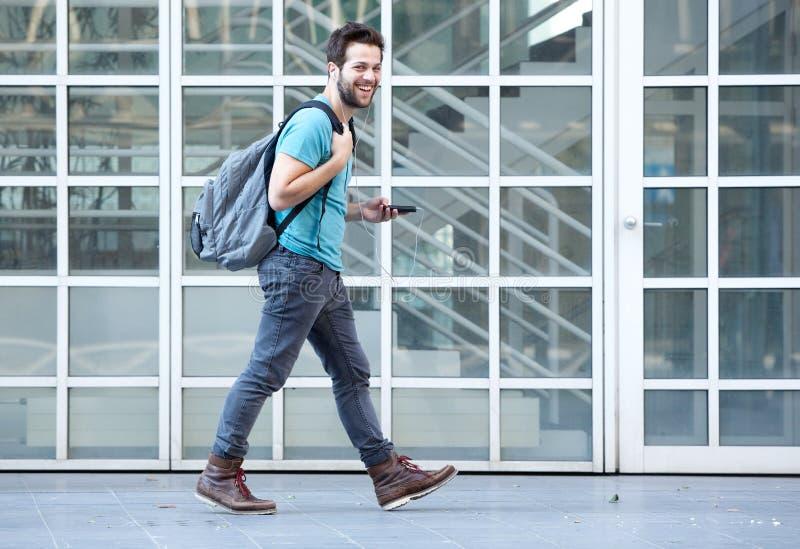 Jonge mens die op stoep met mobiele telefoon en zak lopen stock foto's