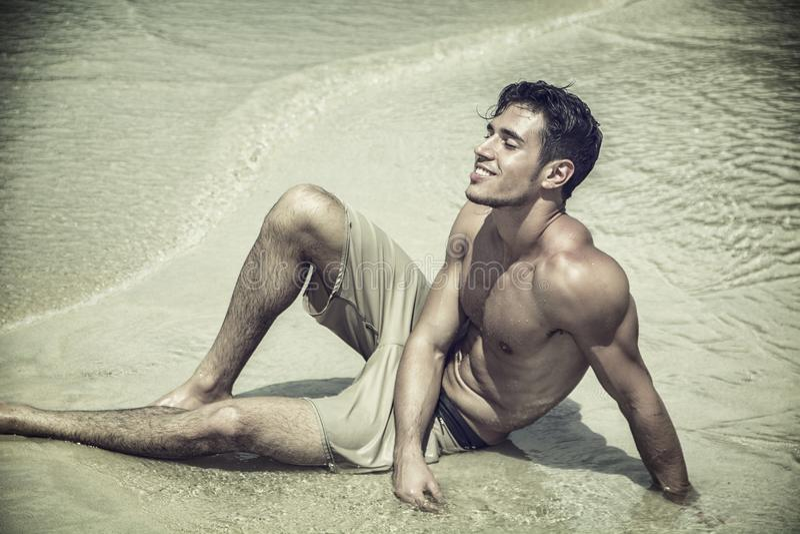Jonge mens die op strand door de oceaan leggen royalty-vrije stock foto