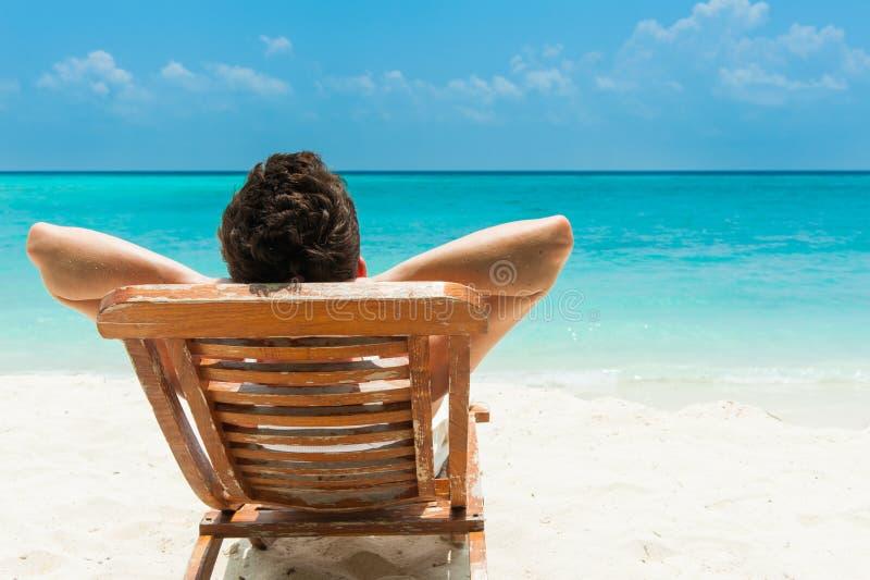 Jonge mens die op strand rusten royalty-vrije stock afbeelding