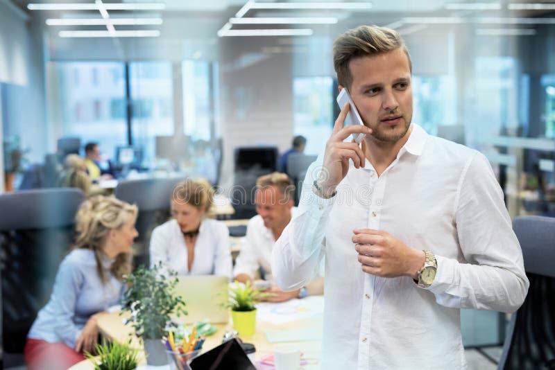 Jonge mens die op telefoon in bureau spreekt royalty-vrije stock afbeeldingen