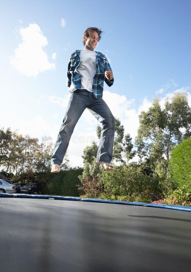 Jonge Mens die op Trampoline springt die in Medio Lucht wordt gevangen royalty-vrije stock fotografie