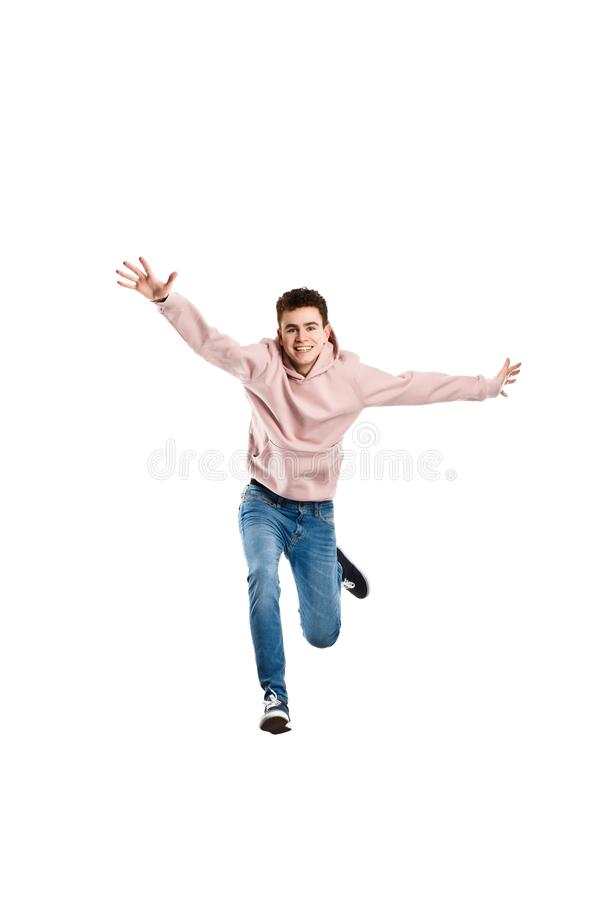 Jonge mens die op witte achtergrond springen stock afbeeldingen
