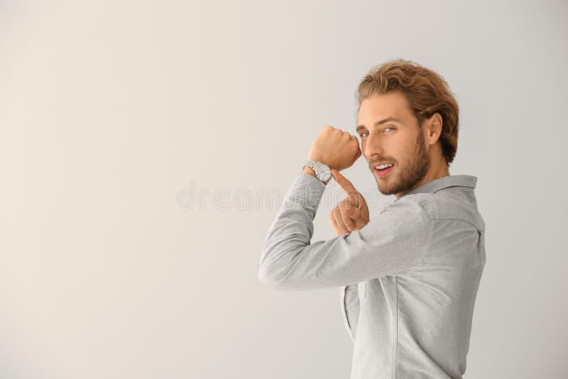 Jonge mens die op zijn horloge op lichte achtergrond richten royalty-vrije stock fotografie