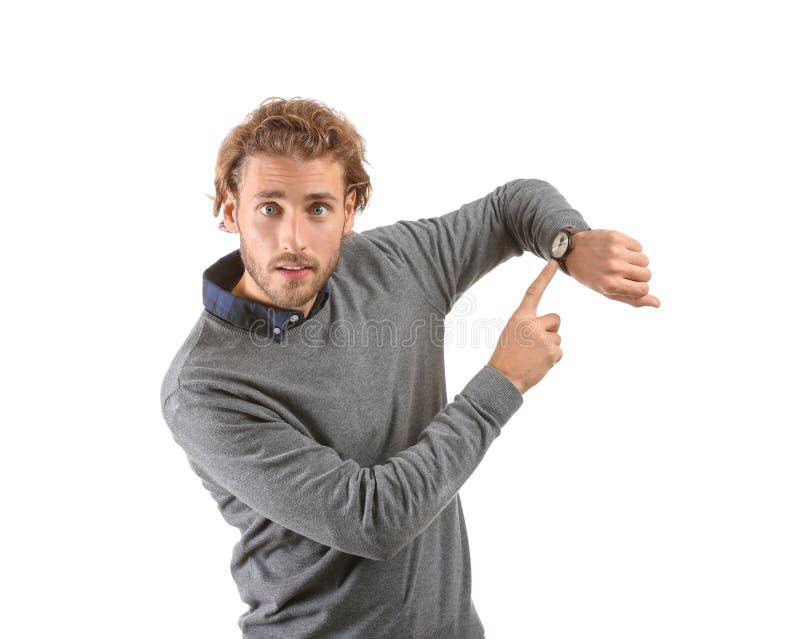 Jonge mens die op zijn horloge op witte achtergrond richten royalty-vrije stock foto's