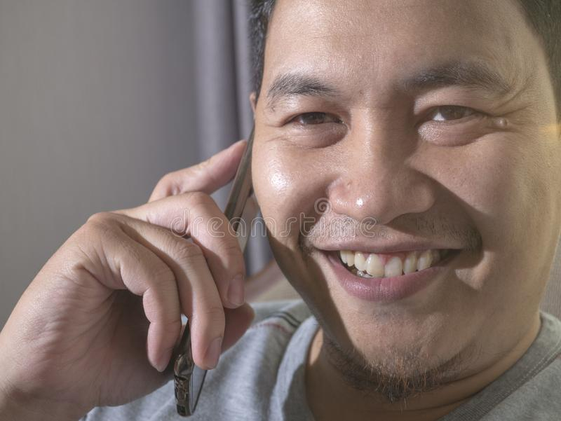 Jonge Mens die op zijn Telefoon, het Gelukkige het Glimlachen Lachen spreken stock foto's