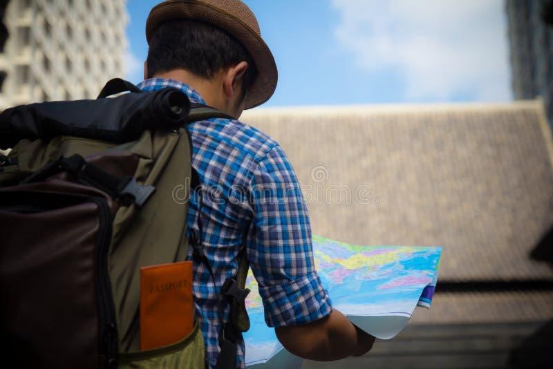 Jonge mens die in open kaart kijken Reiziger die zich met wegenkaart i bevinden stock foto