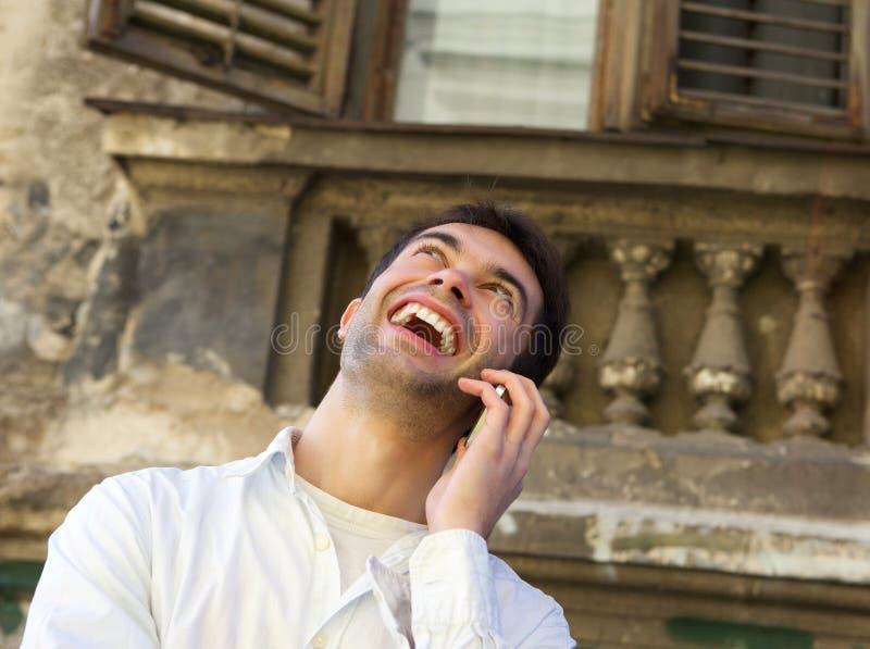 Jonge mens die in openlucht met mobiele telefoon lachen royalty-vrije stock afbeeldingen