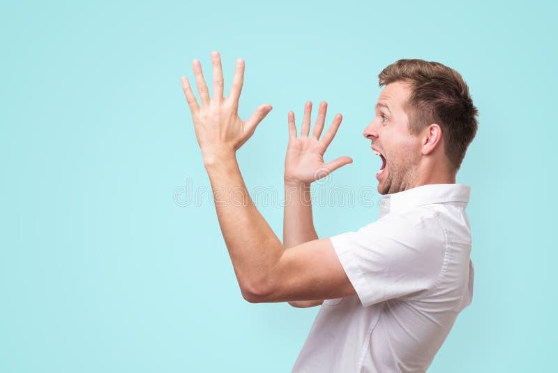 Jonge mens die opzij met handengebaar gillen die op blauwe achtergrond wordt geïsoleerd stock foto