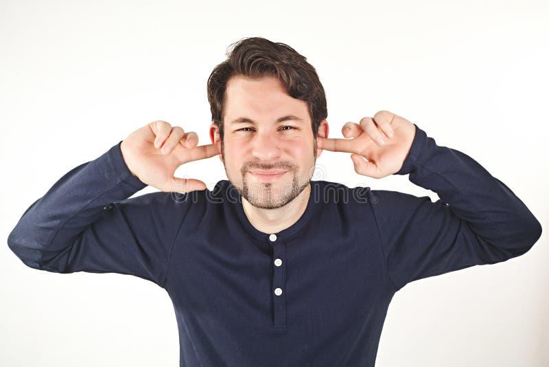 Jonge mens die oren van hevig die lawaai behandelen, op witte backg wordt geïsoleerd stock afbeeldingen