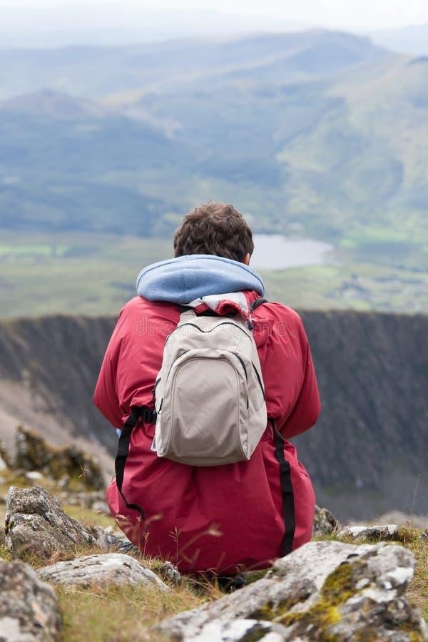 Jonge mens die over bergen kijkt royalty-vrije stock afbeelding