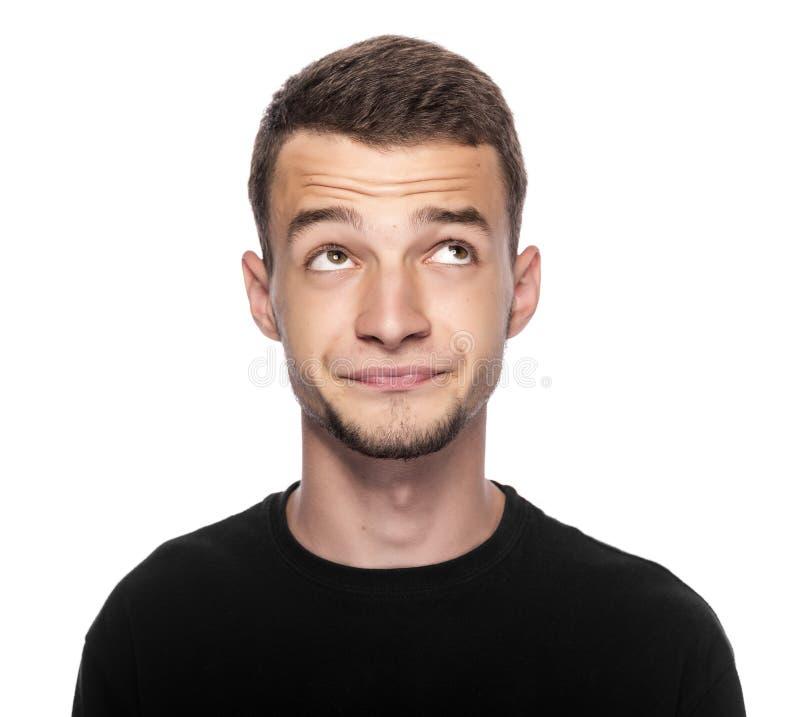 Jonge mens die over prettig iets denken stock foto