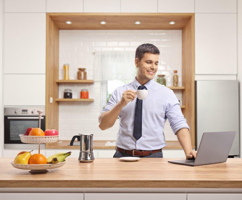 Jonge mens die overhemd en band het drinken espresso draagt en het werken aan laptop in een moderne keuken stock foto's