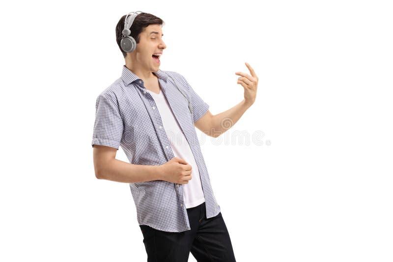 Jonge mens die paar hoofdtelefoons dragen en luchtgitaar spelen stock foto's