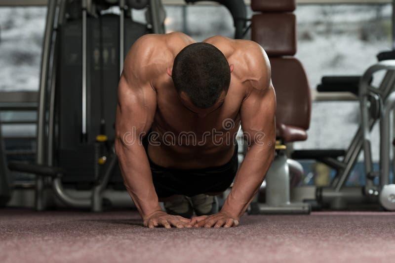 Jonge Mens die Pers UPS in Gymnastiek doen stock foto