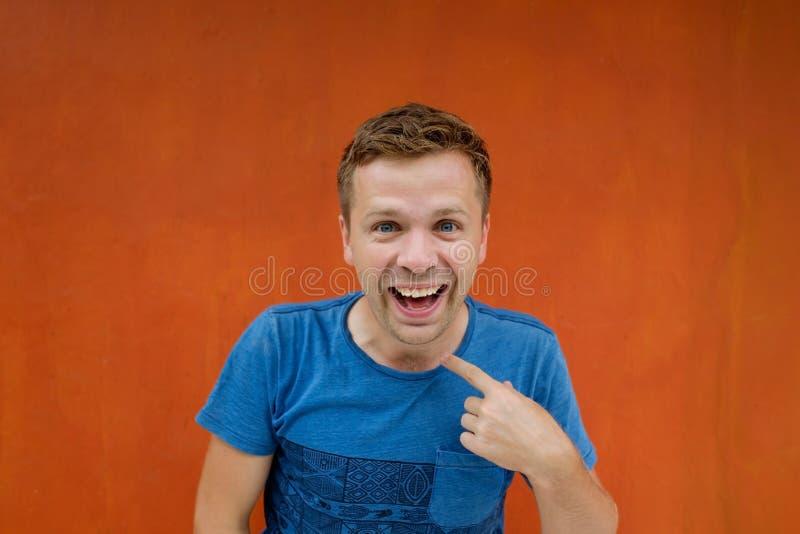 Jonge mens die richten witn wijsvinger op rode achtergrond Hij is gelukkig en glimlachend bij camera royalty-vrije stock afbeelding