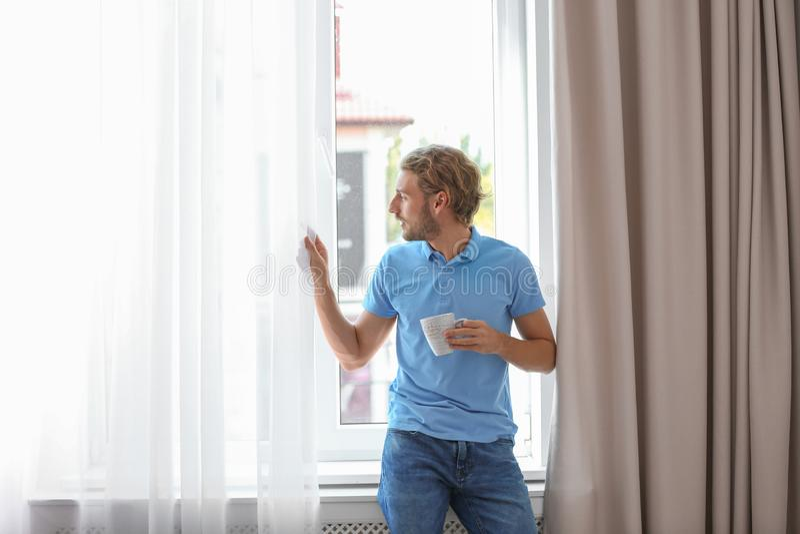 Jonge mens die rust hebben dichtbij venster met open gordijnen royalty-vrije stock afbeeldingen