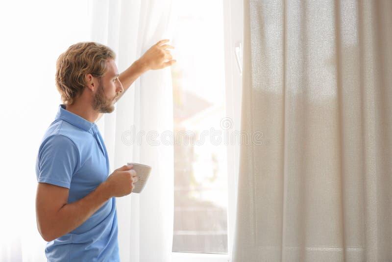 Jonge mens die rust hebben dichtbij venster met open gordijnen stock foto
