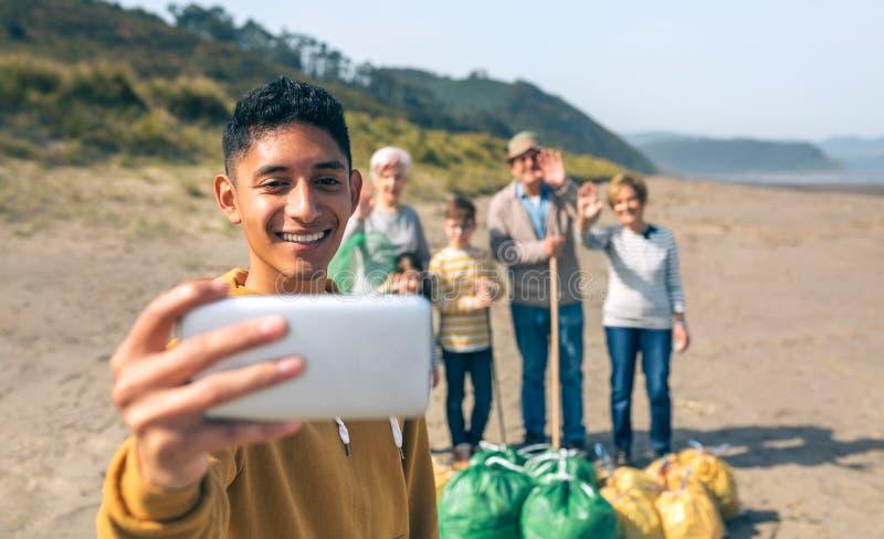 Jonge mens die selfie aan groep vrijwilligers na het schoonmaken van strand nemen royalty-vrije stock foto