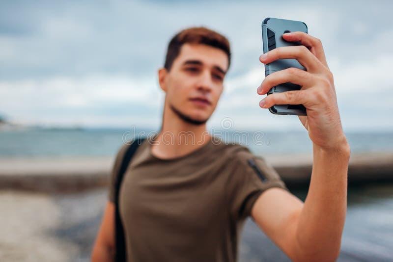 Jonge mens die selfie gebruikend telefoon op bewolkt strand nemen Knappe sportieve kerel die door pijler lopen stock foto's