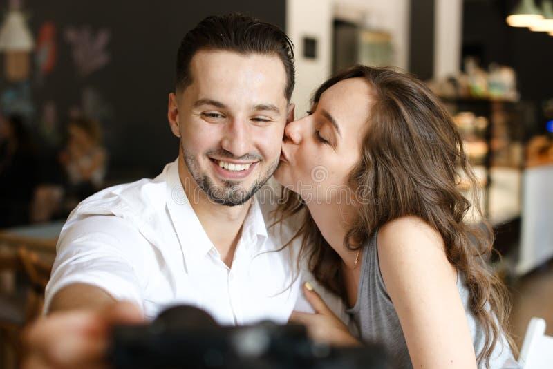 Jonge mens die selfie met het kussen van meisje bij koffie maken stock afbeeldingen