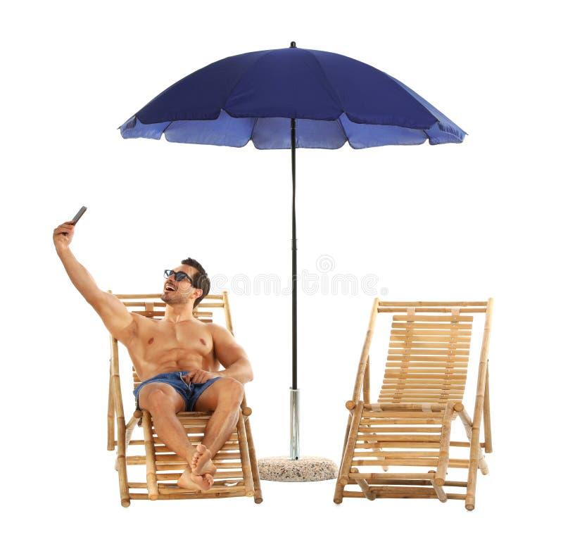 Jonge mens die selfie op zonlanterfanter onder paraplu tegen wit nemen De toebehoren van het strand stock fotografie