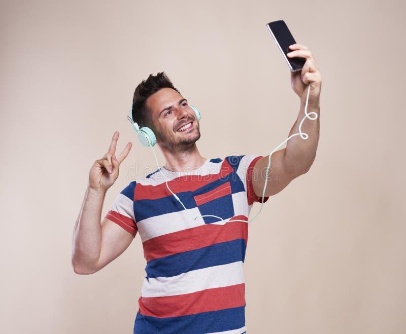 Jonge mens die selfie in studioschot maken royalty-vrije stock afbeelding