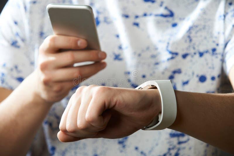 Jonge Mens die Slim Horloge met Mobiele Telefoon synchroniseren royalty-vrije stock afbeelding