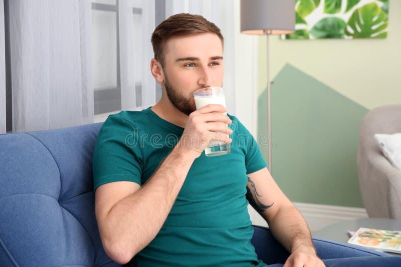 Jonge mens die smakelijke melk drinken stock fotografie