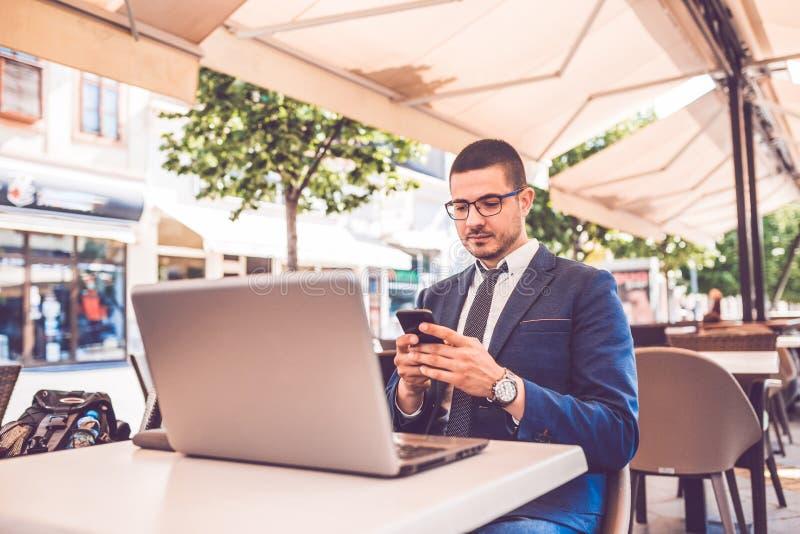 Jonge mens die smartphone en laptop computer in straatkoffie met behulp van stock afbeelding