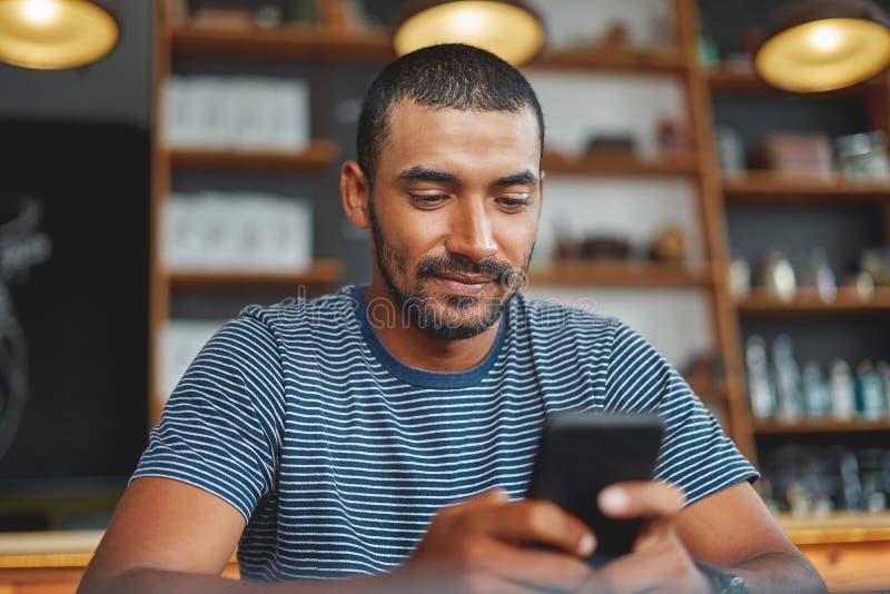 Jonge mens die smartphone in koffiebar gebruiken royalty-vrije stock foto