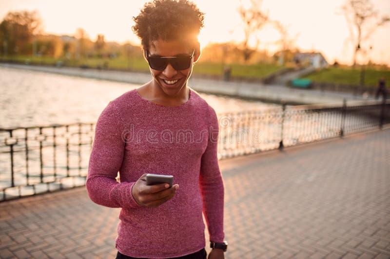 Jonge mens die sms in openlucht met exemplaarruimte schrijven stock foto
