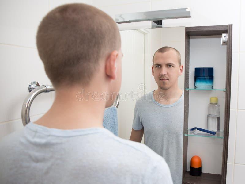 Jonge mens die spiegel in badkamers bekijken stock foto